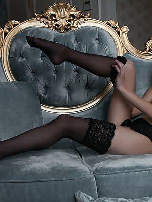 Fascinating Dark Haired Slender Teen Cutie Posing In Alluring Black Stockings On The Sofa.