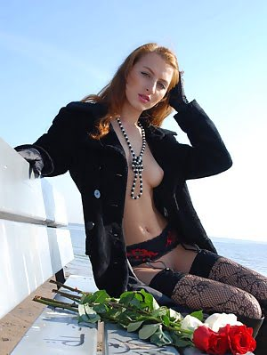 Sexy Redhead Girl Spreads Legs While Posing In Black Coat And Boots.