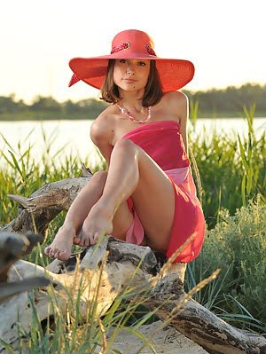 Enchanting Girl In A Hat With A Wide Brim Showing Her Perfect Body Outdoor On The Coast. Outdoor pics