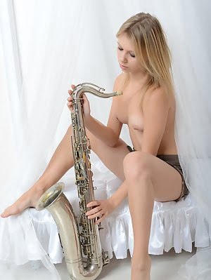 Adorable Shapely Beauty With A Tattoo On Her Right Arm Posing In The Nude With Saxophone. Posing pics