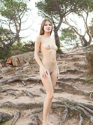 Charming Long Haired Teen Honey With Pretty Face Posing Naked On The Big Roots Of Trees. Posing pics